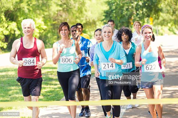 runners approaching finish line during marathon or 5k race - charity benefit stock pictures, royalty-free photos & images