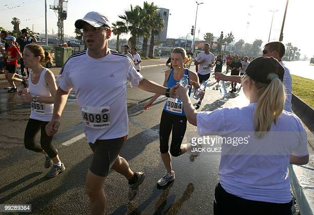 Runners are given water bottles as they compete in the 2010 Tel Aviv Marathon on May 14 2010 AFP PHOTO/JACK GUEZ