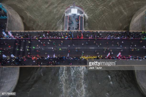 Runners are pictured through the Tower Bridge Exhibition's Glass Floor as they cross the halfway point of the 2017 Virgin Money London Marathon on...