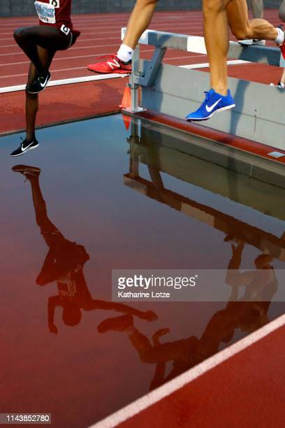 Runners are seen reflected in the water obstacle as they compete in the 3000 meter steeplechase on the first day of the 61st Mt SAC Relays at Murdock...