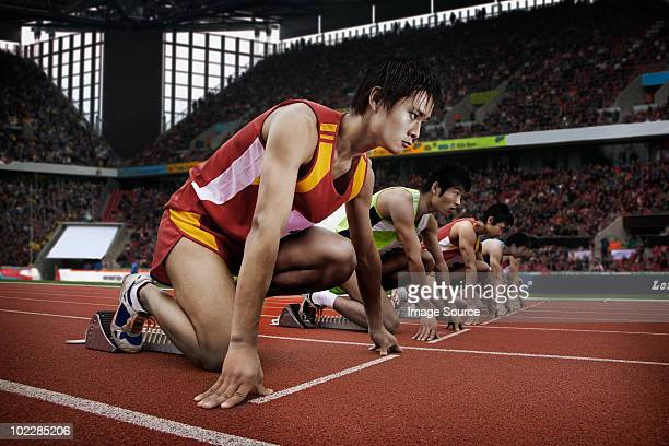 runners at starting line in stadium - athletics stock photos and pictures