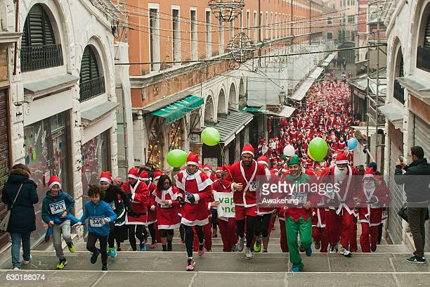 Runners attend at the 3rd Santa Claus Run in Rialto bridge on December 18 2016 in Venice Italy The Santa Claus run is a noncompetitive race involving...