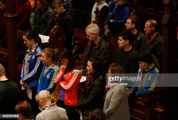 Runners bow their heads during a special The Blessing of the Athletes service at the Old South Church on April 15 the five year anniversary of the...