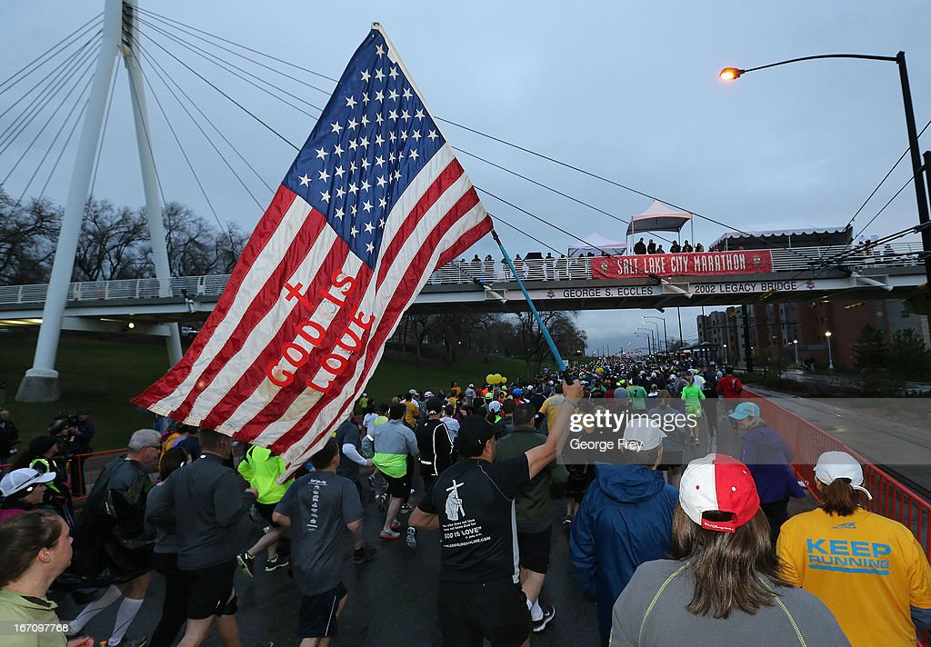 A runners carries an American flag at the start of the Salt Lake City Marathon on April 20, 2013 in Salt Lake City, Utah. Due to the bombings at the Boston Marathon on April 15, security was dramatically increased by law enforcement and Utah National Guard at the Salt Lake City Marathon. Organizers are asking spectators to leave backpacks at home.