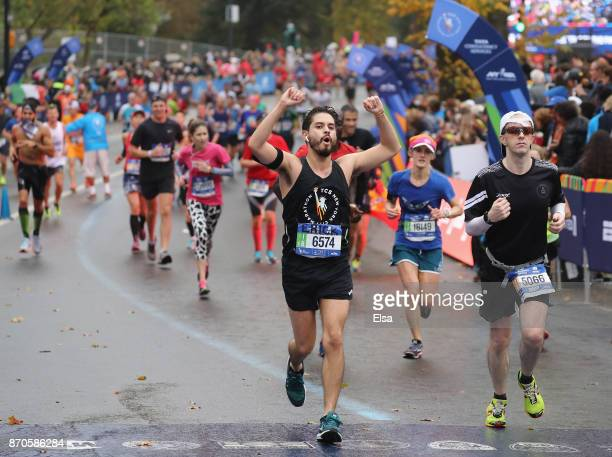 Runners celebrate as they cross the finish line during the TCS New York City Marathon in Central Park on November 5 2017 in New York City
