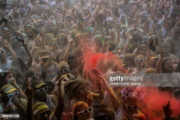Runners celebrate under coloured powder finishing their five kilometers in the Color Run 2018 at the Eiffel Tower in Paris on April 15 2018 Runners...