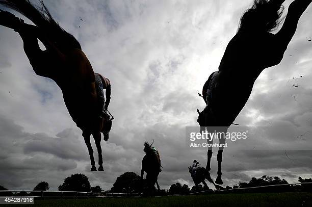 Runners clear a fence in The £500 Permanent Money Backs Handicap Steeple Chase at Fontwell racecourse on August 28 2014 in Fontwell England