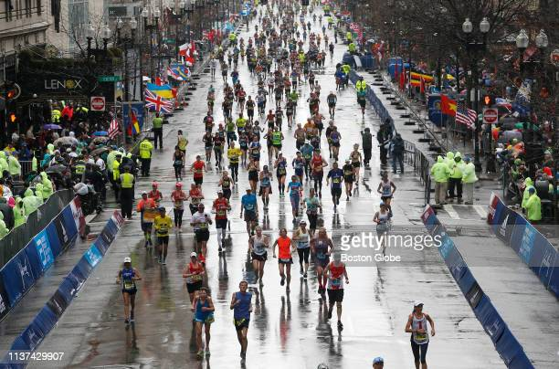 Runners come down Boylston Street in a heavy rain as they make their way towards the finish line of the 123rd Boston Marathon on April 15 2019