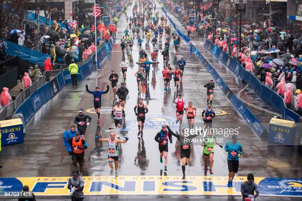 Runners come to the finish line of the 122nd Boston Marathon where rain and high winds battered down for the duration Monday April 16 2018 / AFP...