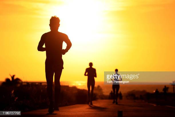 Runners compete as the sun sets during the Ironman World Championships on October 12 2019 in Kailua Kona Hawaii