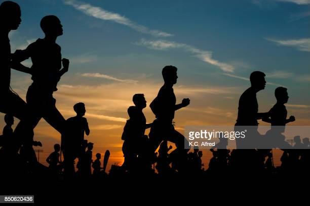 runners compete in a 5k at sunset in corona, california. - maratona foto e immagini stock