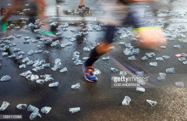 TOPSHOT Runners competing in the Berlin Marathon make their way through discarded drinks cups at the 23km mark on September 16 2018 in Berlin