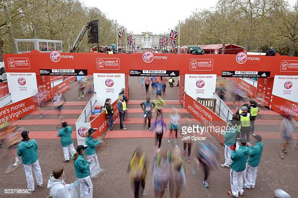 Runners cross the finish line on The Mall at the Virgin Money London Marathon on April 24 2016 in London England