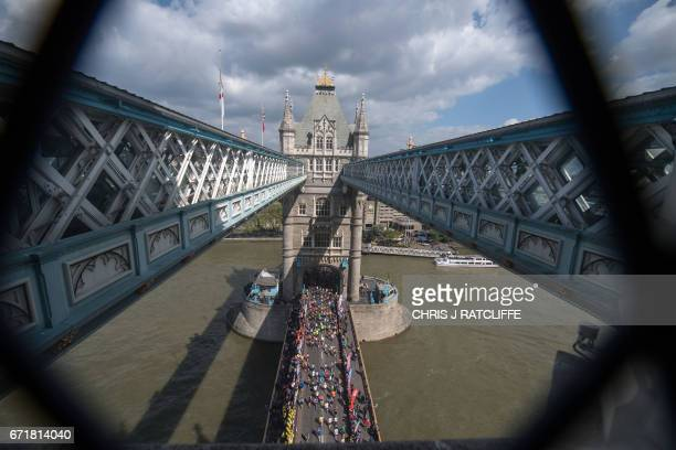 TOPSHOT Runners cross the half way point on Tower Bridge during the London Marathon in London on April 23 2017 / AFP PHOTO / CHRIS J RATCLIFFE