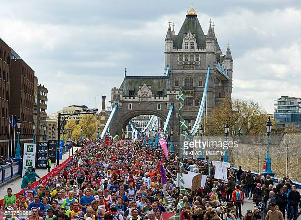 Runners cross Tower Bridge as they take part in the 2016 London Marathon in central London on April 24 2016 / AFP / NIKLAS HALLE'N