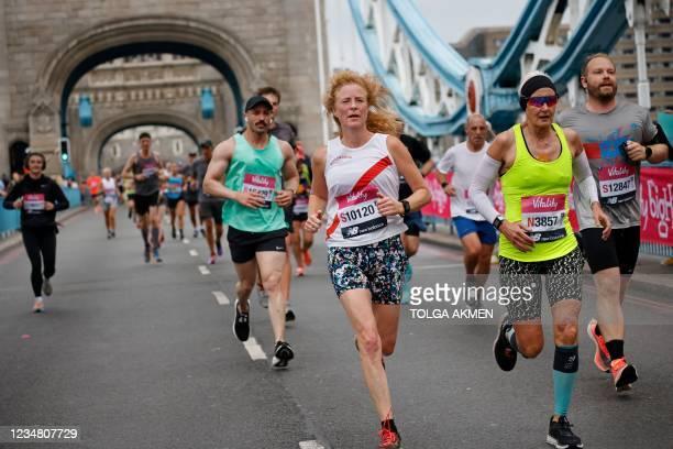 Runners cross Tower Bridge during the 2021 Big Half Marathon in central London on August 22, 2021. - The Vitality Big Half was originally scheduled...