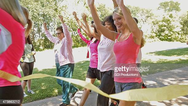 runners crossing finish line in breast cancer awareness marathon race - charity benefit stock pictures, royalty-free photos & images