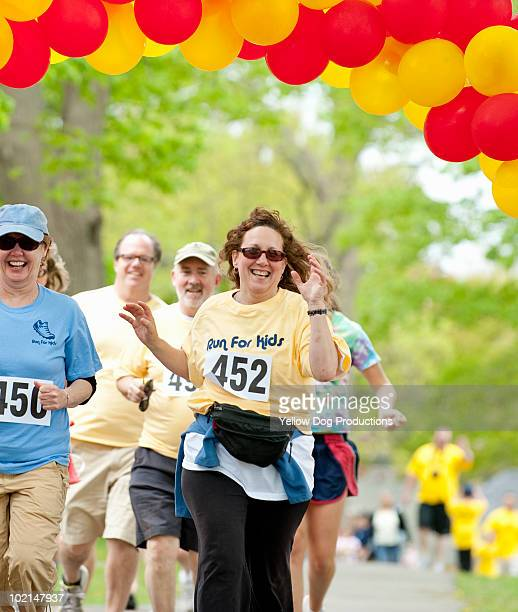 Runners crossing the finish line at a charity race