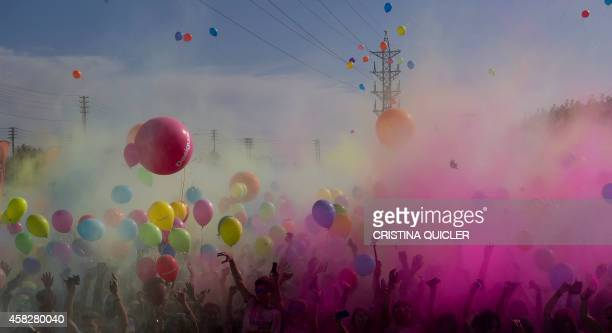 Runners dance after taking part in the Color Run of Sevilla on November 2 2014 The Color Run is a race where participants are showered with colored...