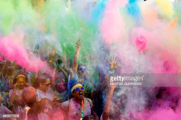 Runners dance and cheer after the Color Run race considered the world's most joyful 5km race in which every kilometre a powder of a different dye is...