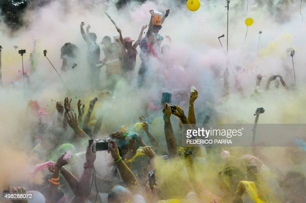Runners dance covered in coloured powder after taking part in the Color Run of Caracas on November 22 2015 / AFP / FEDERICO PARRA