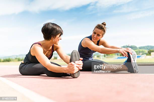 runners doing stretching on the track