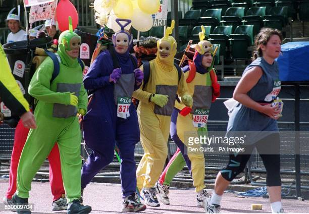 Runners dressed as teletubbies approach the finishing line of the London Marathon today Photo by Ben Curtis/PA