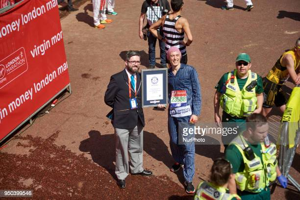 Runners dressed in fancy costumes receive a Guinness Record Certificate during the Virgin Money London Marathon in London England on April 22 2018