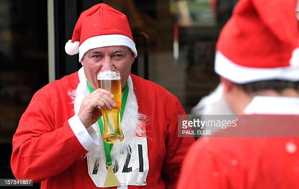 A runners dressed in Father Christmas costumes drinks beer after competing in the annual five kilometer Santa Dash in Liverpool northwest England on...