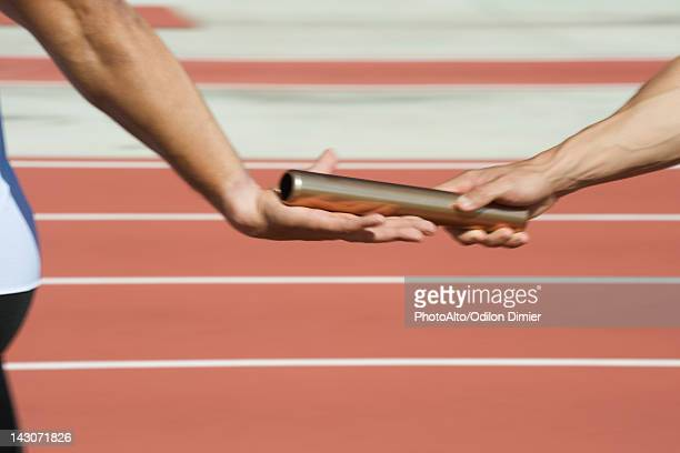 runners exchanging baton in relay race, cropped - リレー ストックフォトと画像