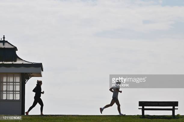 Runners exercise on the seafront at Goring-by-Sea on the south coast of England, on April 26 during the national lockdown due to the novel...