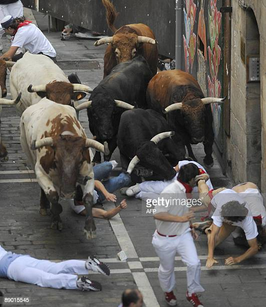 Runners fall in front of Nuñez del Cuvillo fighting bulls on the last San Fermin Festival bull run on July 14 in Pamplona northern Spain The festival...