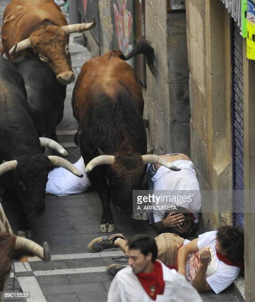 Runners falls in front of Nuñez del Cuvillo fighting bulls on the last San Fermin Festival bull run on July 14 in Pamplona northern Spain The...