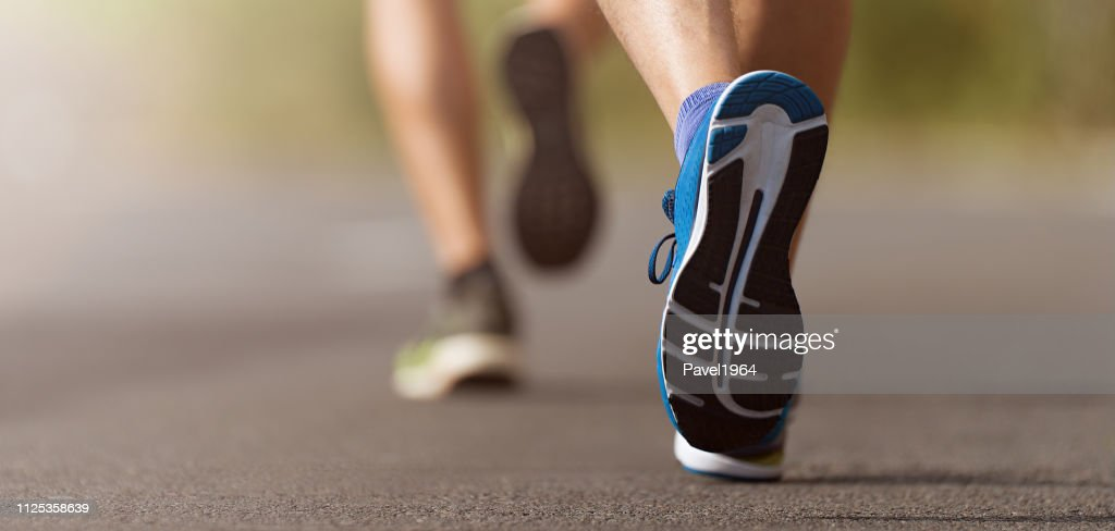 Runners feet running on road close up on shoe : Stock Photo
