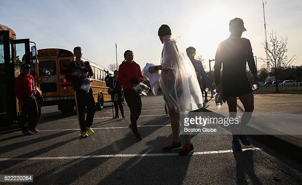 Runners get off of buses as they arrive at the Athletes' Village prior to the running of the 120th Boston Marathon in Hopkinton Mass on April 18 2016