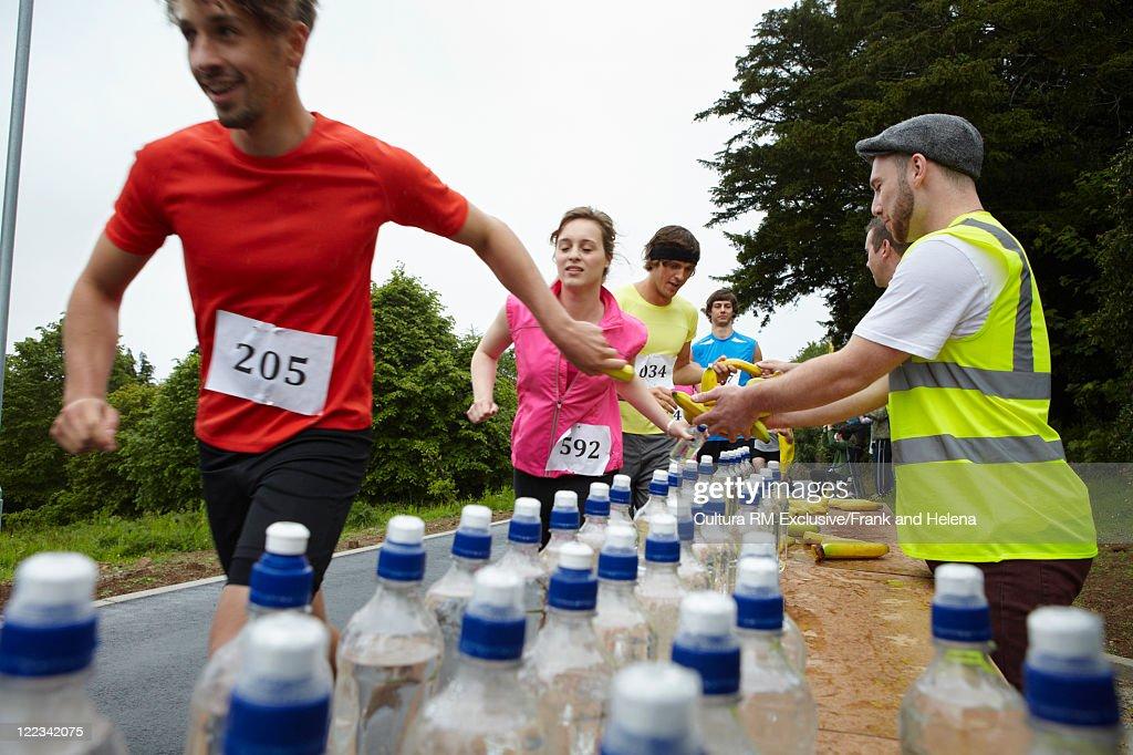 Runners having bananas in marathon : Stock Photo