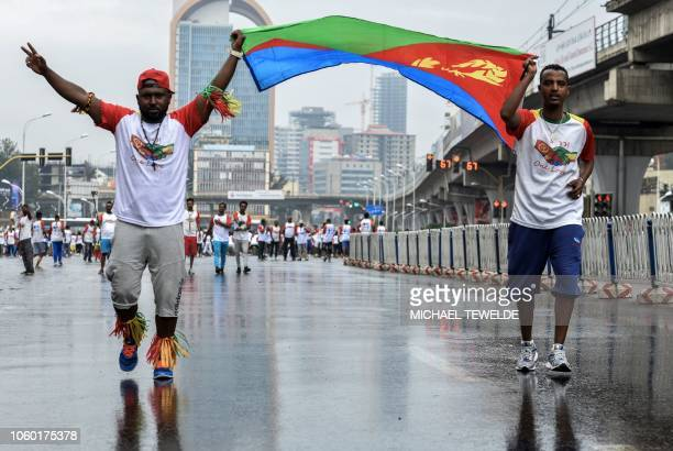 Runners hold Eritrea's national flag during the first EthiopiaEritrea Peace and reconciliation Run in Addis Ababa on November 11 2018 Thousands of...
