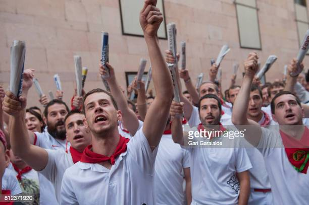 Runners hold up newspapers while they sing to an image of San Fermin before the start of the running of the Jandilla's fighting bulls during the...