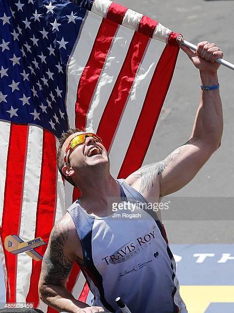 A runners holds an American flag during the 2014 BAA Boston Marathon on April 21 2014 in Boston Massachusetts