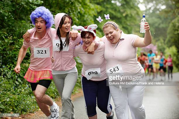 runners in costume racing in marathon - marathon stock pictures, royalty-free photos & images