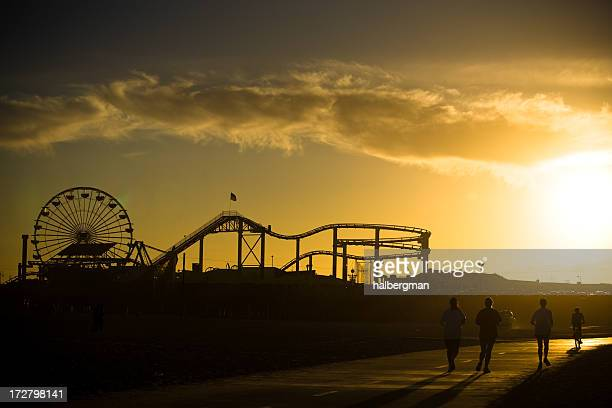 runners in front of the santa monica pier - santa monica stock pictures, royalty-free photos & images