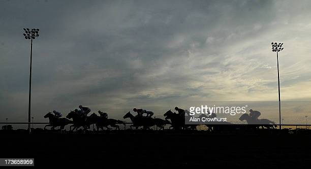 Runners in The £25 Free Bet At BetVictorcom Maiden Stakes race down the back straight at Kempton Park racecourse on July 16 2013 in Sunbury England