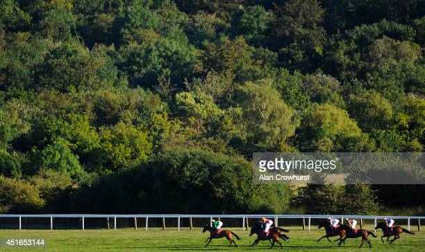 Runners in The EBF Stallions Arthur Budgett Memorial Maiden Fillies' Stakes make their way down the back straight at Epsom racecourse on July 03,...