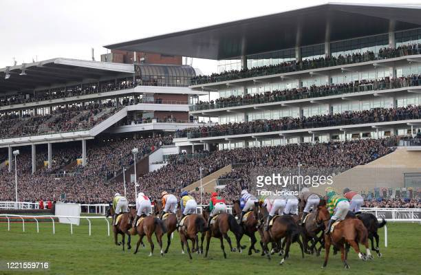 Runners in the first race pass by the packed main stands during day four of the Cheltenham National Hunt Racing Festival at Cheltenham Racecourse on...