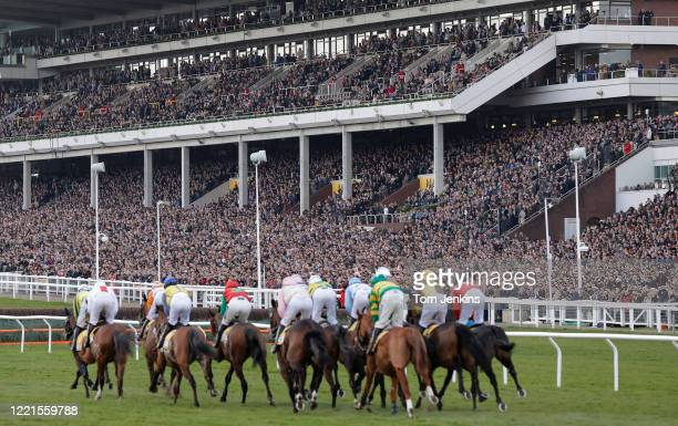 Runners in the opening race pass by the packed main stand during day four of the Cheltenham National Hunt Racing Festival at Cheltenham Racecourse on...