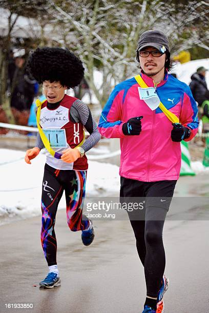 Runners, including one with an afro wig , at the 14th annual Manno Relay Marathon held at Sanuki Manno National Government Park in snowy conditions....