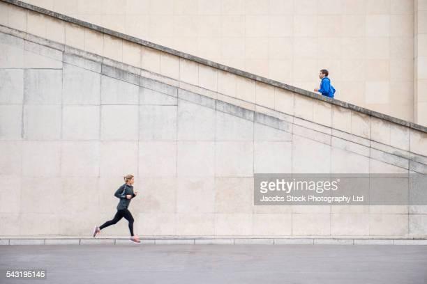 runners jogging near staircase - courir photos et images de collection
