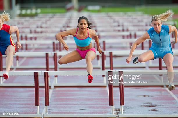 Runners jumping hurdles in race