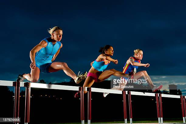 runners jumping hurdles in race - hurdling stock photos and pictures