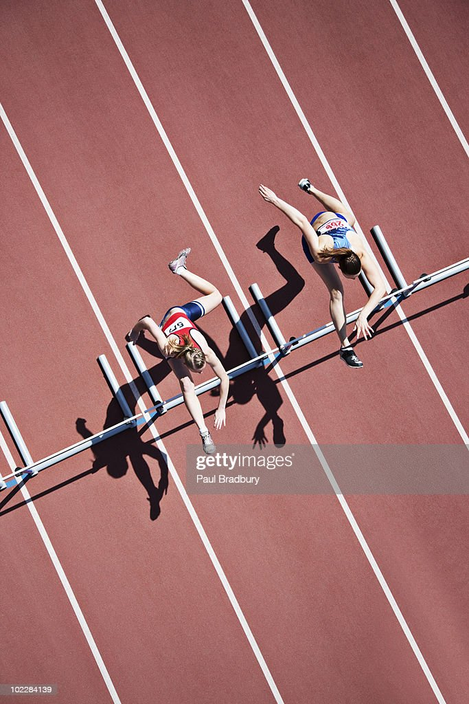 Runners jumping hurdles on track : Stock Photo